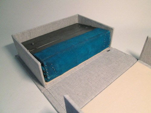 A Coptic binding with welded metal covers and a blue deerskin spine, in a grey cloth box with cream paper tray linings