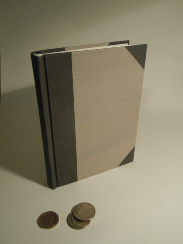 A half grey cloth case binding with paper sides with a subtle paste paper pattern