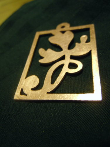 A sheet of copper with the silhouette of a leaf shape cut out in a rectangular border